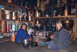Our hosts by their stove, manufactured in Tibet, with Yak cheeses drying above
